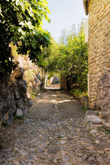 Long small cobblestone alley in the old medieval village of Labeaume in France