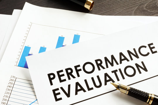 Documents about performance evaluation on a desk.