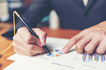 Close up hands signing terms of agreement documents of businessman on his desk, business signing concept