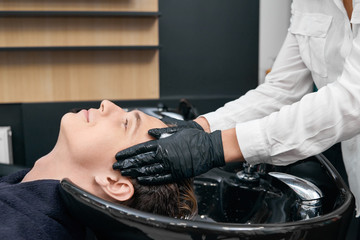 Hairdresser' s hands washing client's hair in beaty salon's sink. Boy sitting with his head laying in the black ceramic sink with closed eyes. Feeling good, relaxing. Hairdresser wearing black gloves.