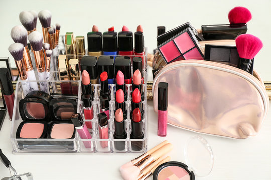 Set of cosmetic products and brushes on table