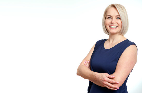 Attractive middle aged woman with folded arms on white background