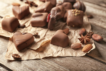 Yummy chocolate candies on wooden table