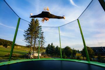 Junges Mädchen auf Trampolin - Spagat im Sprung