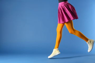 Legs of beautiful young woman wearing tights and skirt on color background Wall mural