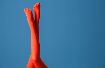 Legs of beautiful young woman in bright tights on color background