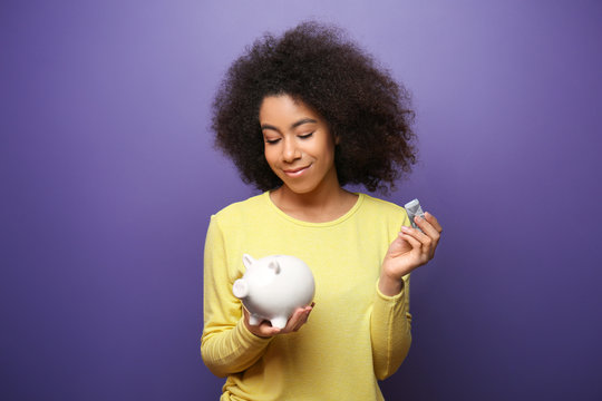 Young African-American woman with money and piggy bank on color background. Savings concept