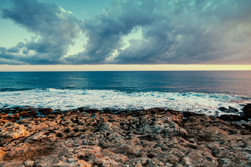 Fototapete - Beautiful colorful sunset on the stone beach, the image with retro toning, blue waves and clouds