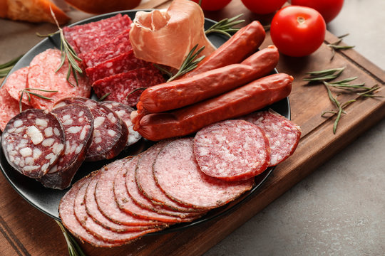 Plate with assortment of delicious deli meats on wooden board