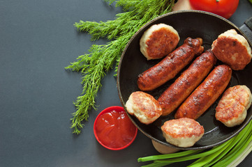 meat cutlets, sausages, tomato and tomato sauce, greens and green onionon black background with copyspace, domestic food or domestic cooking concept