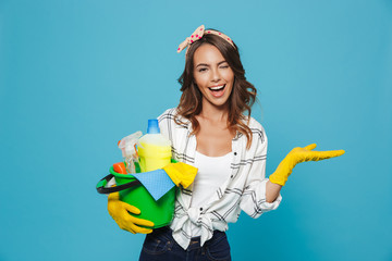 Obraz Portrait of smiling happy housewife 20s wearing yellow rubber gloves for hands protection holding bucket with cleaning supplies, isolated over blue background - fototapety do salonu