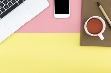 Flat lay of smart phone, laptop, notebook, pen and a cup of coffee with copy space on pastel yellow and pink background.