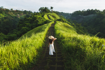 Autocollant pour porte Lieu connus d Asie Young beautiful woman walking on Campuhan Ridge way of artists, in Bali, Ubud. Beautiful calm sunny morning