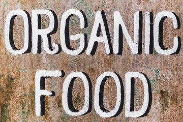 "Wooden textured board with painted handwritten text ""Organic food"" in cafe"