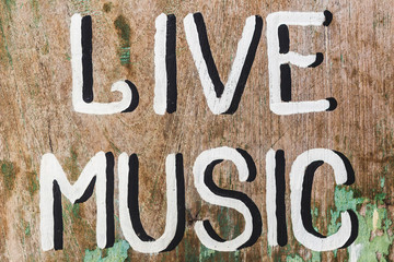 "Wooden textured board with painted handwritten text ""Love Music"" in cafe"