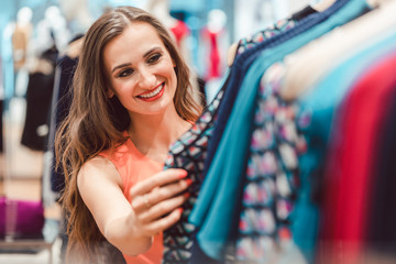 Woman browsing through dresses on rack in fashion store looking happy