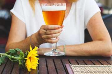 Woman sitting in outdoor restaurant and drinking beer, city life in summer