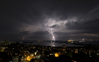 Spectacular Thunderstorm in dark night sky above city