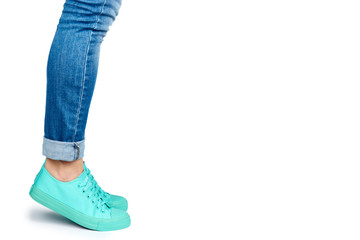 Female leg in jeans and sneakers isolated on white background, copy space template