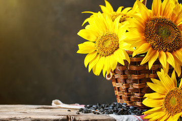 Wall Mural - Beautiful sunflowers in a basket on a wooden table.