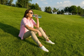 Adult woman in sunglasses drinks water from bottle on sunny summer day sitting on green grass in park.
