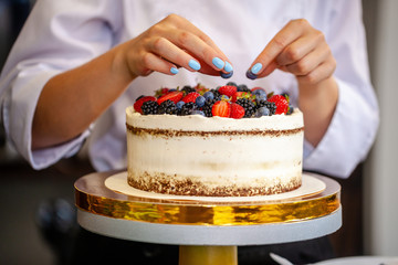 Girl chef cooks confectioner, decorates cake with forest berries. concept making without lactose cakes. Copy space, selective focus
