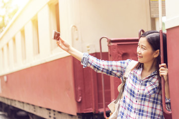 happy young Asian traveller woman taking selfie photo from mobile phone at train station while traveling