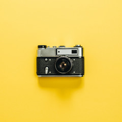 Vintage retro camera isolated on yellow background. Flat lay, top view.