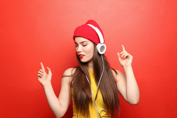 Attractive hipster girl listening to music on color background