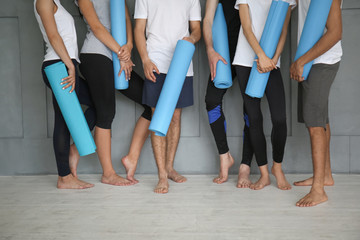Keuken foto achterwand Fitness Group of sporty people with yoga mats near grey wall