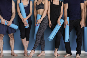 Keuken foto achterwand Fitness Group of people with yoga mats near color wall
