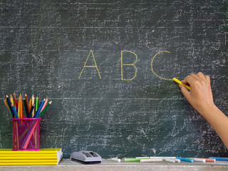 Back to school concept. Hand writing on the blackboard with stationery and notebooks in front of blackboard.