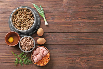 Bowls with pet food and natural products on wooden background