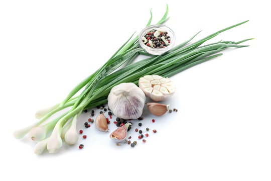 Composition with green onion, garlic and spices on white background