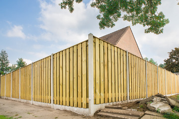 New wooden fence at garden of house