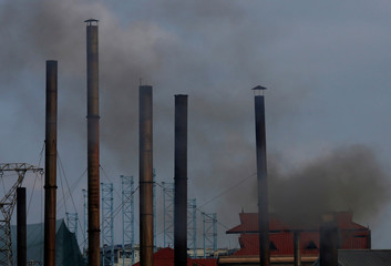 Smoke rises from the chimney of a paper factory outside Hanoi