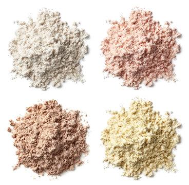 Four various heaps of protein powder (vanilla, strawberry, chocolate, banana)