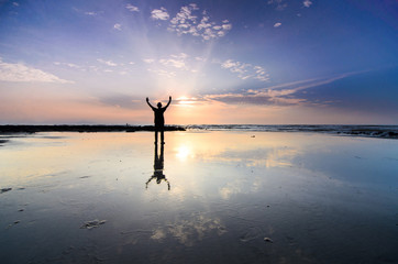 Silhoutte of man raise hand above facing the sunrise with water reflection Wall mural