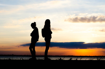 Couple woman silhouette standing sad  during sunset and beautiful sky.