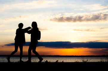 Couple woman silhouette hug because nostalgia during sunset and beautiful sky.