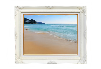 Antique white photo frame with Landscape view of Beautiful beach and tropical sea isolated on white background.