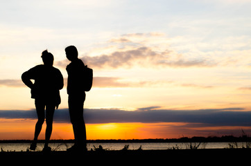 Couple woman silhouette standing very happily talking during sunset and beautiful sky.