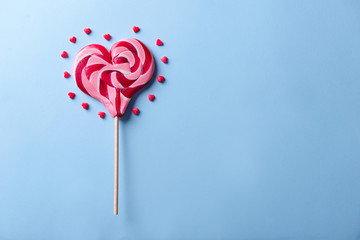 Tasty heart-shaped lollipop on color background
