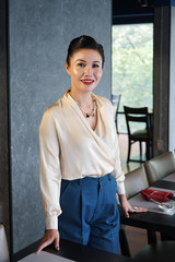 Beautiful smiling Asian female in elegant blouse and pants standing between restaurant tables and looking at camera