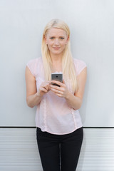Attractive blond woman holding a mobile phone