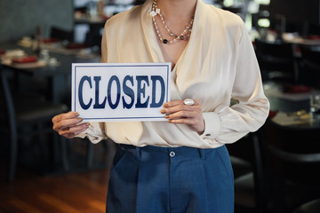 Crop view of waitress in light elegant clothes and necklace showing white Closed sign in hands on blurred background