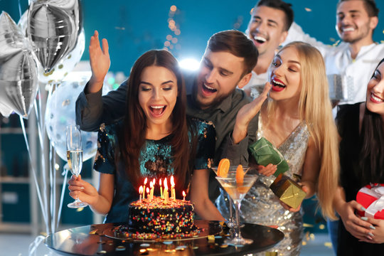 Young woman with friends near her birthday cake at party in club