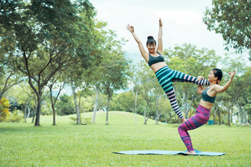 Gorgeous young Asian females in Acroyoga flag pose, one of them standing on stretch mat and another standing on shoulder and hip with raised up arms looking at camera and smiling on blurred background