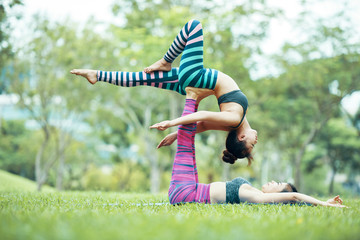 Side view of young Asian women practicing Acroyoga in park, female base lying on grass with raised up legs supporting back of lying in back bird pose flyer with stretched out leg on blurred background