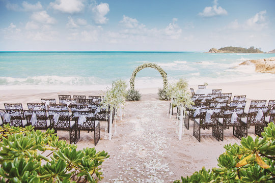 Beautiful beach wedding venue setting with flowers, floral decoration on arch, panoramic ocean view